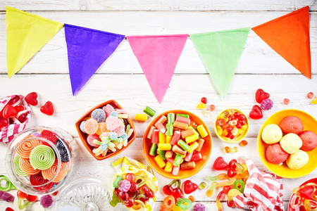confections: Overhead view of table set with party flags in pink, green and yellow besides bowls of yummy colorful confections Stock Photo