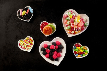 confect: Overhead view of heart shaped bowls with candy, licorice rolls and gum drops against a black background