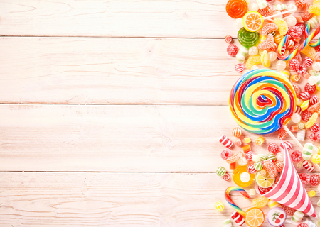 Muy grande remolino coloreado por lechón caramelos de goma y piruletas con sabor a fruta al lado de envoltura en forma de cono despojado lleno de otros productos de confitería