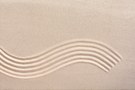 curving lines: Curving wave pattern raked into smooth manicured sand in a Japanese zen garden for meditation and tranquility with copy space above