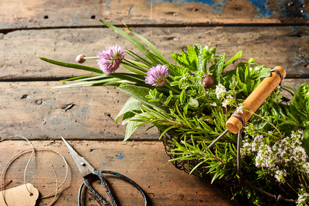 Top down first person perspective view on various herbs in basket with scissors and tag on table for floral arrangement concept