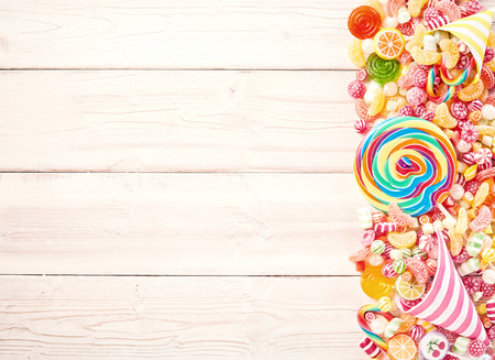 child birthday: Background of wood slat table piled with sweets to one side with extra large spiral shaped sucker and fruit flavored gummy slices