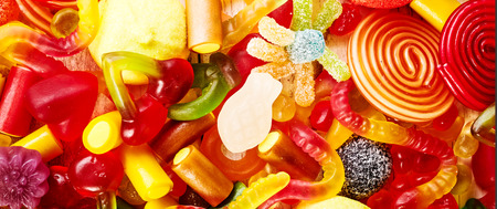 confections: Background of yummy colorful candies, gummy worms and other delicious confections in a pile