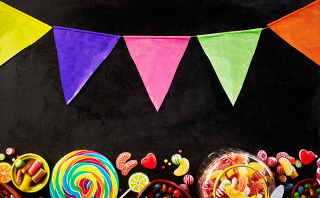 string top: Black background with string of party flags on top and jar filled with hard confections on bottom next to other delicious candies Stock Photo
