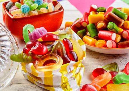 candies: Cierre de vista de gusanos de goma en la bolsa despojado además de platos de deliciosos dulces establecido sobre una mesa de madera rústica