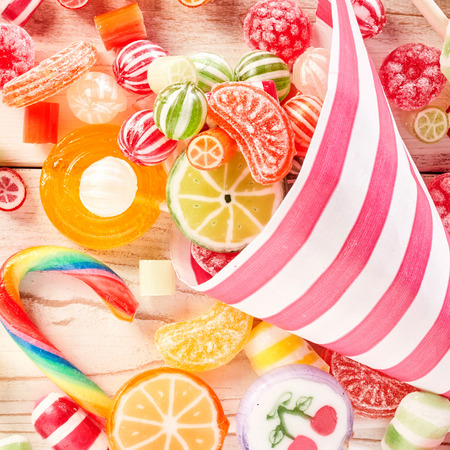 confections: Close up of tasty confections wrapped in stripped paper besides swirl colored candy canes and fruit flavored gummy slices