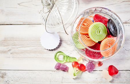 Overhead close up view of licorice rolls in open glass jar and besides a handful of gummy candies