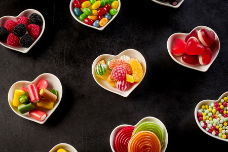 ceramic heart: Rows of ceramic heart shaped bowls with candies and tasty gum drops, licorice rolls and jelly beans