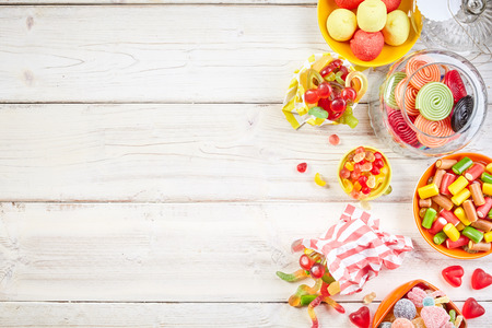 confections: Overhead view of bowls filled with candy and other yummy confections beside glass jar with rolled licorice Stock Photo