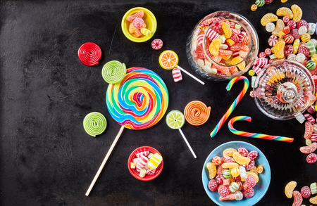 fruit candy: Jar filled with delicious gummy fruit slices besides stripped candy canes, hard confections and lollipops against a black background Stock Photo