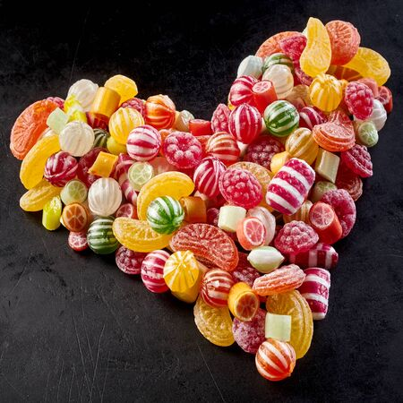 confect: Colorful assortment of boiled fruity sweets, jujubes and striped peppermints arranged as a heart over a black background in square format Stock Photo