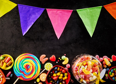 candy border: Festive carnival poster with colorful bunting and an assorted of rainbow colored candy as a border over a dark slate background Stock Photo