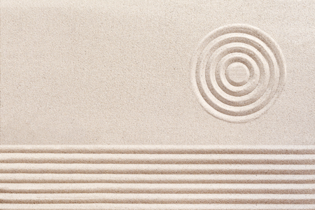 raked: Simple spiritual patterns in a Japanese Zen Garden with concentric circles and parallel lines raked n the manicured smooth sand Stock Photo