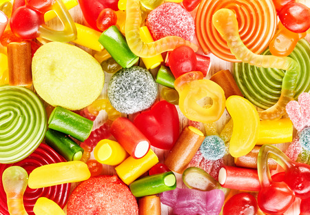 Colorful background of delicious candies, licorice rolls, fruit flavored gummy slices and other yummy confections