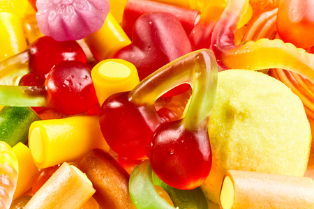 confect: Background texture of a mixture of bright colorful jujubes and gummy candy in different shapes in a close up full frame view Stock Photo