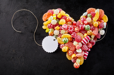 affixed: Long string with white tag affixed to heart made of tasty hard candies and fruit flavored gummy slices Stock Photo
