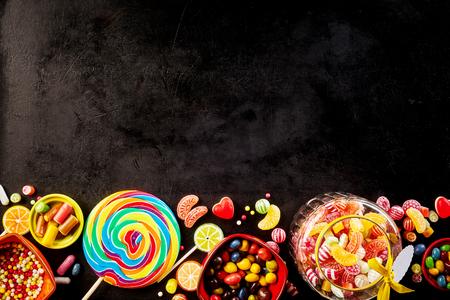 Zwarte achtergrond met rij van gebak aan de onderkant met grote spiraal gekleurde zuignap en glazen pot gevuld met harde snoepgoed