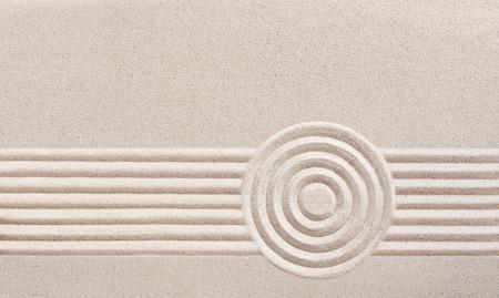 Japanse Zen-tuin met raked zand in een minimalistische patroon van parallelle lijnen en concentrische cirkels voor meditatie Stockfoto