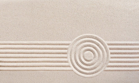 Japanese zen garden with raked sand in a minimalist pattern of parallel lines and concentric circles for meditation