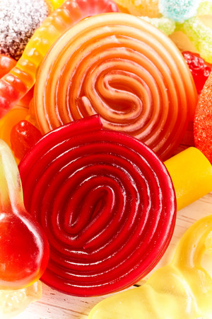 confect: Colorful red and orange swirled spiral gummy candy in a close up view amongst an assortment of jujubes for a childhood treat Stock Photo