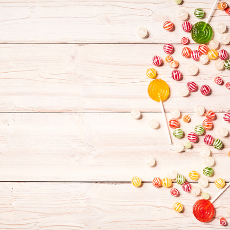confections: Background of wood table with confections on it such as yellow, green and red lollipops besides round stripped candy Stock Photo