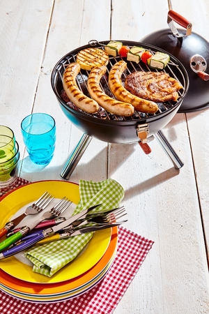 haloumi: Colorful picnic plates and utensils at a barbecue on a white wooden deck with meat and kebabs grilling over the fire in the summer sun