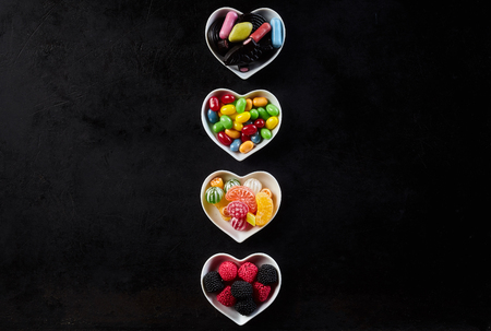 ceramic heart: Row of ceramic heart shaped bowls on black and filled with tasty hard candies, gum drops and jelly beans Stock Photo