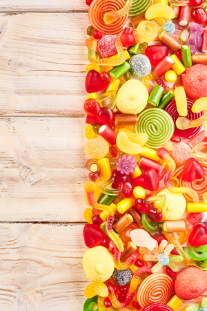 confections: Background of half filled wood table with candies, licorice rolls, fruit flavored gummy slices and other yummy confections