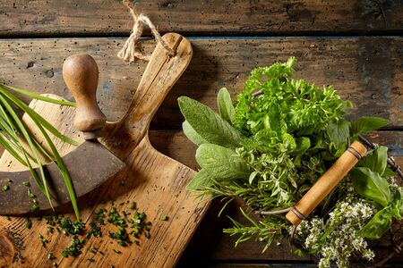 potherb: Top down first person perspective view on various herbs in basket beside cutting board on table for food preparation
