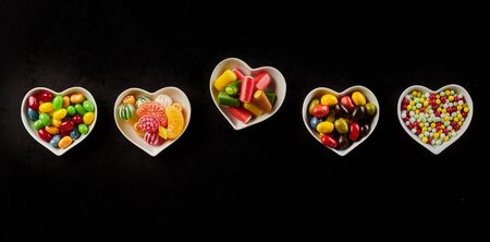 offset angle: Yummy hard candies in row of ceramic heart shaped bowls against a black background