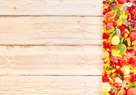 confections: Background of wood slats with candy at its end in a pile with licorice rolls and other delicious gummy confections