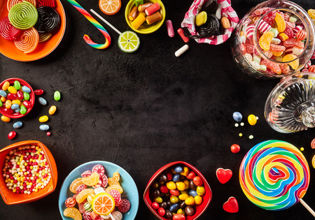 candy hearts: Frame of colorful bright assorted candy in bowls and jars, candy canes and rainbow colored spiral lollipops on black with scattered candy hearts and jellybeans around a central copy space on slate