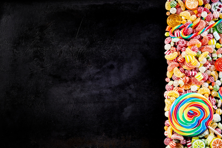 confect: Black background with pile of candies to one side featuring stripped spiral shaped sucker and other fruity hard confections