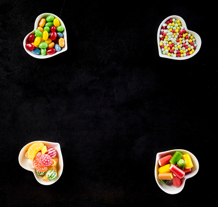 confections: Black background with ceramic bowls at its corners each filled with delicious hard candies, jelly beans and other yummy confections Stock Photo