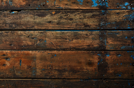 Old dark vintage wood background texture with dents and stains in a full frame view for use as a design template