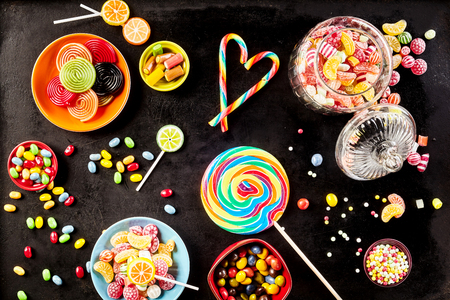 candy shop: Bowls of yummy jelly beans and licorice rolls besides large sucker, jar filled with hard candies and small lollipops against a black background