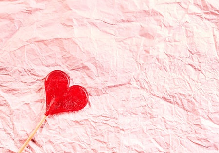 crinkled: Textured pink crinkled paper Valentines background with a red heart-shaped lollipop in one corner and plenty of copy space for a message to a loved one Stock Photo