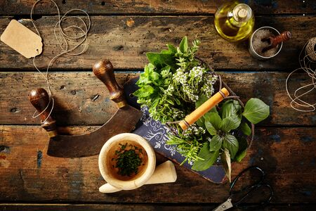 top down: Top down first person perspective view on various herbs, oil, pestle, blank tag and mezzaluna over old wooden table Stock Photo