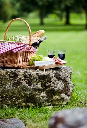 pan y vino: Un picnic colocado sobre una roca en un parque verde de la primavera con una cesta de mimbre con una botella de vino tinto y baguette junto a una tabla de quesos, salchichas picantes y uvas frescas, bajo ángulo de vista