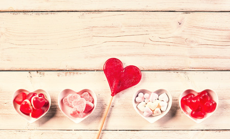 confect: Rustic wood background with bowls along bottom filled with tasty gum drops and a heart shaped lollipop between them