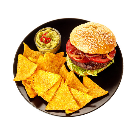 sesame seed bun: Top down view on isolated round black plate of triangular tortilla chips, guacamole and burger in sesame seed bun over white background