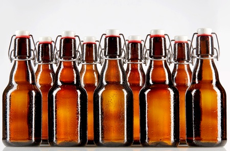 abreast: Two rows of nine tall blank glass bottles with copy space used for beer or other commercial beverages over gray background Stock Photo