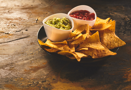 tortilla chips: Single serving of delicious crunchy appetizer of triangular yellow corn tortilla chips beside little bowls of guacamole and salsa dip