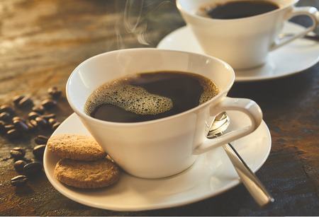 Freshly poured cup of espresso coffee served with cookies in an elegant modern white cup and saucer with scattered coffee beans alongside