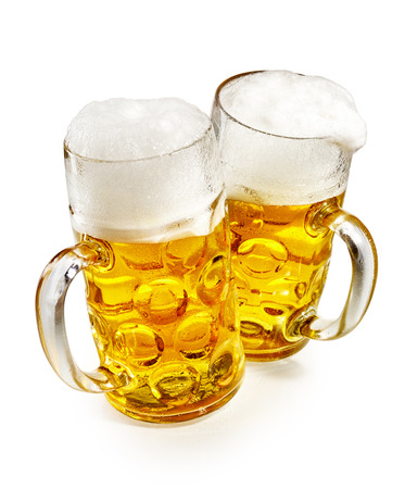 Two pint mugs of glowing golden frothy cold beer viewed high angle over white conceptual of the annual German Oktoberfest