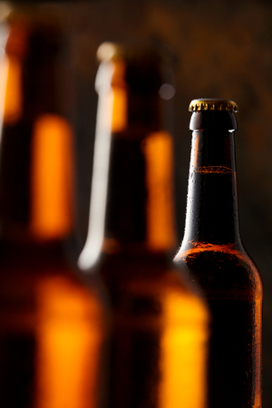 unlabelled: Glowing unlabelled beer bottles in the darkness of a pub or tavern over the Oktoberfest with selective focus to the neck of a bottle in the background Stock Photo