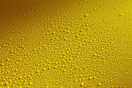 droplets: Glistening water drops beading on a waxed or polished yellow metal surface such as a car bonnet in rain or mist