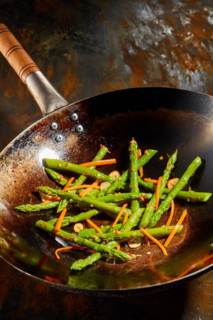 discolored: Healthy fresh cooked green asparagus tips and carrots in an old discolored frying pan on an old rusty metal surface