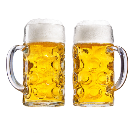 stein: Two glass tankards of chilled beer with a good frothy head side by side with the handles in opposite directions isolated on white conceptual of the Oktoberfest Stock Photo