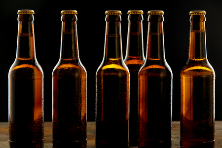 unlabelled: Row of ice cold unlabelled unopened brown beer bottles standing on a pub or tavern counter on a shadowy background in a branding and advertising concept for Oktoberfest Stock Photo